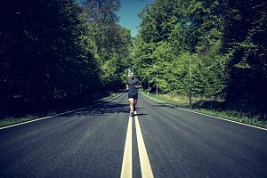 Fit young man in sportswear running along a country road