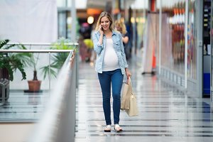 Pregnant woman in shopping center making phone call