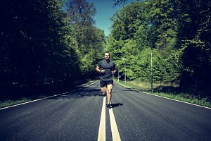 Fit young man running up a road in the country