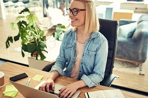 Smiling young businesswoman using a laptop at her office desk