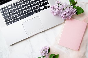 Feminine workspace mock up with laptop keyboard and lilac flowers