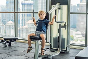 The boy does exercises in a fitness room