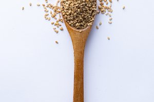 Spoon full of sesame grains on white