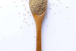 Spoon full of quinoa grains on white
