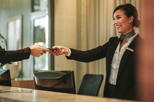 Smiling receptionist attending hotel