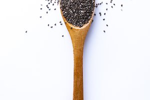 Spoon full of chia grains on white b