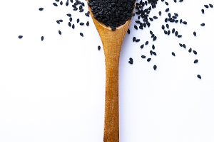 Spoon full of balck sesame grains on