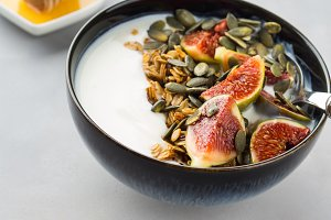 Healthy breakfast yogurt bowl with granola and fig