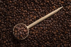 Wooden spoon with roasted coffee bea