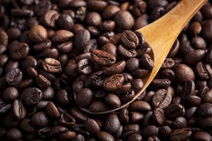 Roasted coffee beans on wooden spoon