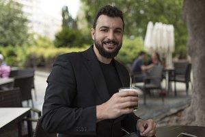 Man drinking beer in bar terrace looking at camera