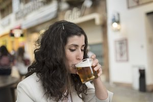 Woman drinking beer in bar terrace