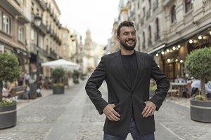 Posing bearded mid adult elegant suit man in european street