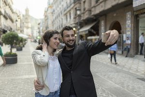 Mid adult couple taking self portrait in european city