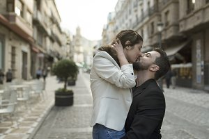 Mid adult couple kissing in the street