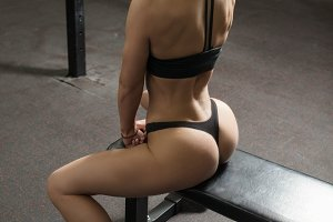 A beautiful sporty brunette is sitting in the gym