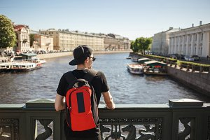 Stylish male tourist with backpack looking to cityscape on the embankment of Griboyedov canal in St. Petersburg, Russia