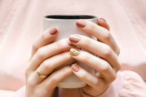 Female hands with beige nail design.