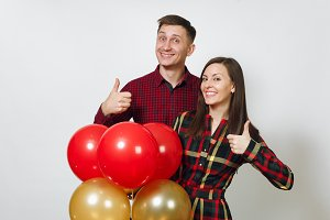 Beautiful caucasian young happy smiling couple in love. Woman and man in plaid checkered clothes with red, yellow balloons, showing thumbs up on white background isolated. Holiday, party concept.