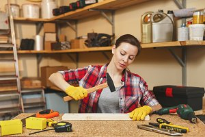 Pretty caucasian young brown-hair woman in plaid shirt, gray T-shirt, yellow gloves working in carpentry workshop at wooden table place with different tools, hammering nails into board with hammer.