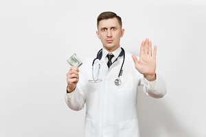 Serious doctor man isolated on white background. Male doctor in medical uniform showing stop gesture with palm, holding bundle of dollars, banknotes cash money. Healthcare personnel, medicine concept.