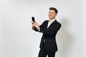 Young smiling successful handsome business man in black suit doing selfie on modern mobile phone isolated on white background for advertising. Concept of achievement, career and wealth in 25-30 years.