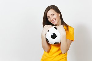 Beautiful European young cheerful happy woman, football fan or player in yellow uniform hugging soccer ball isolated on white background. Sport, play football, health, healthy lifestyle concept.