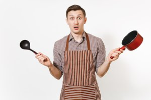 Young surprised man chef or waiter in striped brown apron, shirt holding red empty stewpan black ladle isolated on white background. Male housekeeper or houseworker. Kitchenware and cuisine concept.