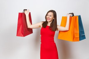 Attractive glamour caucasian fashionable young brown-hair woman in red dress holding multi colored packets with purchases after shopping isolated on white background. Copy space for advertisement.