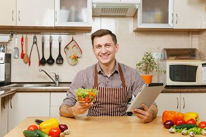 Handsome smiling caucasian young man in apron, brown shirt sitting at table with vegetable salad in bowl and tablet in light kitchen. Dieting concept. Healthy lifestyle. Cooking at home. Prepare food.