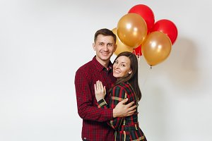 Beautiful caucasian young happy smiling couple in love. Woman and man in plaid checkered clothes with red, yellow balloons, celebrating birthday, on white background isolated. Holiday, party concept.