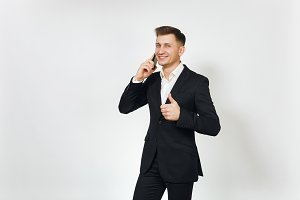 Young successful handsome business man in black suit talking on mobile phone, showing thumb up isolated on white background for advertising. Concept of achievement, career and wealth in 25-30 years.