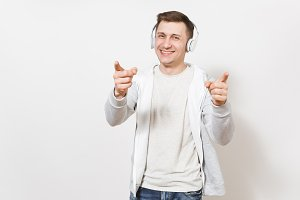 Young handsome fun smiling man student in t-shirt and light sweatshirt listening to music with white wireless headphones and shows fingers in camera isolated on white background. Concept of emotions