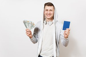 Young handsome smiling happy man in t-shirt, light sweatshirt with hood, headphones holds international passport, bundle of dollars, cash money isolated on white background. Concept of travel, tourism