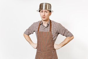 Fun man in striped apron with silver stainless glossy aluminium empty stewpan, pan or pot on head isolated on white background. Male housekeeper or houseworker. Kitchenware, dishes, cuisine concept.