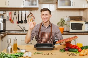Handsome caucasian young man in apron sitting at table with pieces of meat, vegetables, showing OK gesture, cooking at home preparing meat stake from beef in light kitchen full of fancy kitchenware.