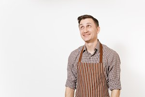 Young smiling man chef or waiter wearing striped brown apron, shirt posing isolated on white background. Male housekeeper or houseworker looking up on copy space. Domestic worker for advertisement.