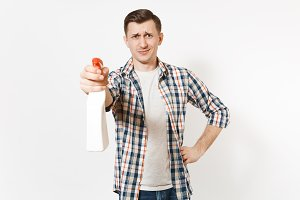 Young housekeeper man in checkered shirt holding white blank empty cleaning spray bottle with cleaner liquid isolated on white background. Male doing house chores. Copy space for advertisement.