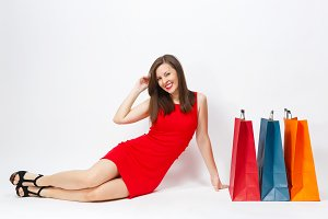 Attractive glamour caucasian fashionable young brown-hair woman in red dress sitting at multi colored packets with purchases after shopping isolated on white background. Copy space for advertisement.