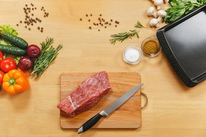 Raw meat. Fresh beef tenderloin on cutting board on wooden table with different vegetables, spices, mushrooms, dill, basil, rosemary, baking tray, knife. Top view flat lay Copy space for advertisement