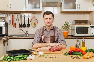 Handsome caucasian young man in apron sitting at table with vegetables, cooking at home preparing meat stake from pork, beef or lamb, in light kitchen with wooden surface, full of fancy kitchenware.