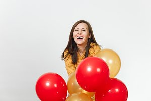 Beautiful caucasian fun young happy woman in yellow clothes with shy charming smile, red, golden balloons, celebrating birthday, on white background isolated for advertisement. Holiday, party concept.