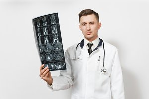 Serious handsome young doctor man holds x-ray radiographic image ct scan mri isolated on white background. Male doctor in medical uniform, stethoscope. Healthcare personnel, health, medicine concept.