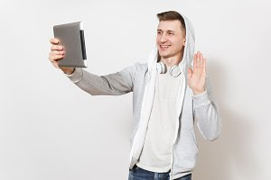 Young handsome smiling man in blue jeans, t-shirt, light sweatshirt with hood, headphones waving hand and photographs himself on tablet pc computer isolated on white background. Concept of technology