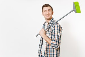 Young smiling housekeeper man in checkered shirt holding green broom for sweep on shoulder isolated on white background. Male doing house chores. Copy space for advertisement. Cleanliness concept.