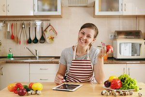 A young woman siting by the table and looking for a recipe in the tablet in the kitchen. Vegetable salad. Dieting concept. Healthy lifestyle. Cooking at home. Prepare food.