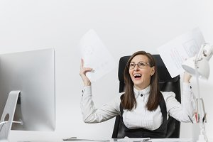 Pretty angry business woman in suit sitting at the desk with documents, working at computer with modern monitor in light office, swearing and screaming, resolving issues, on white background