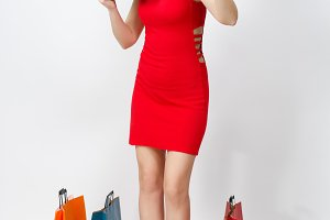 Full length attractive glamour fashionable young woman in red dress holding cash dollars, multi colored packets with purchases after shopping isolated on white background. Copy space for advertisement