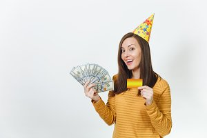 Caucasian young happy woman in yellow clothes, birthday party hat holding wad of cash money, golden credit card, celebrating holiday on white background isolated for advertisement. Winner with dollars