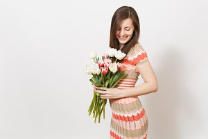 Beautiful young brunette girl in light patterned dress is holding bouquet of white and pink tulips in hands, rejoices and looks at flowers in studio on white background. Concept of holiday, good mood.
